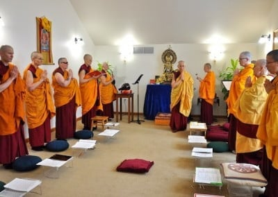 The sangha stand respectfully as the abbess returns to her bowing cushion.