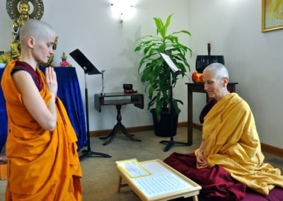A young Buddhist nun stands before a seated nun