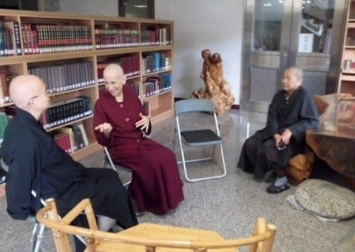 three nuns talking in library