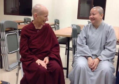 two nuns sitting and smiling