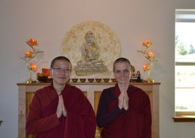 Two nuns pose with Buddha statue