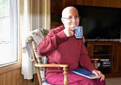Nun siting in chair drinking tea