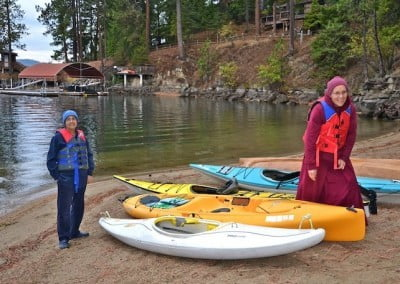 nun and woman with kayaks on beach