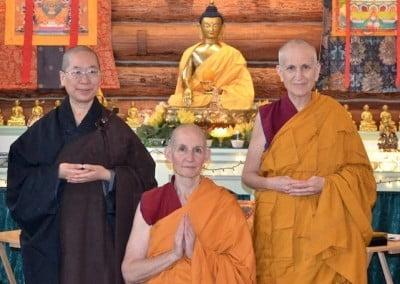 Three nuns pose wit Buddha statue