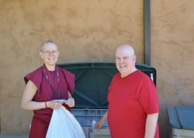 Buddhist nun and lay person collecting recycling