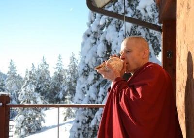 A Buddhist monk blows a conch