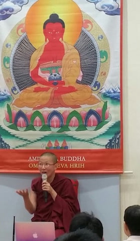 A Buddhist nun speaks into a microphone