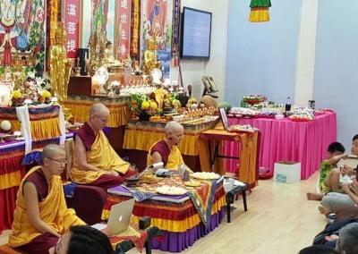 Buddhist nun sits before a shrine, teaching
