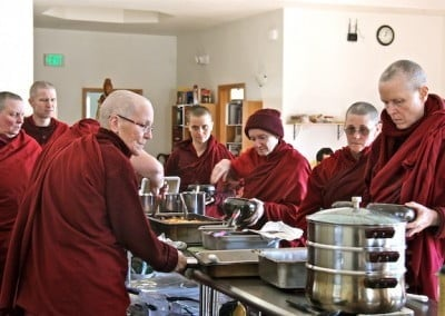 A group of Buddhist nuns around a table filled with food