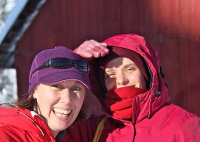Two women wearing coats and hats smile at the camera