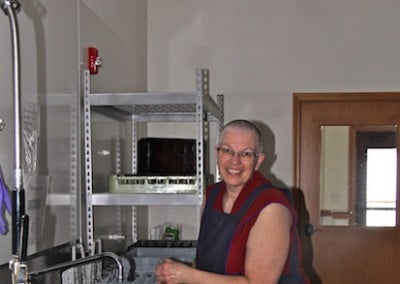 A Buddhist nun in the kitchen laughs