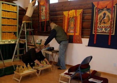 Tsundru, John, and Lynn give the meditation hall a spring cleaning before Geshe-la arrives.