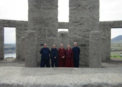 Five Abbey travelers standing at Stonehenge on the Columbia River, a replica of the original erected as a peace monument and memorial to the local men who died in WWI.