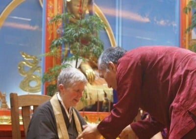 Yangsi Rinpoche bending forward and makes an offering to Roshi Jan Chozen Bays from Great Vow Monastery.