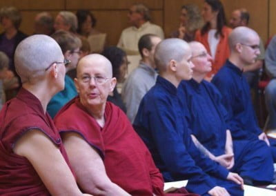 Abbey community sitting in a row, Venerable Jigme and Venerable Chonyi talking to each other.