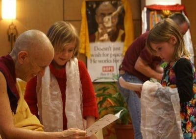 A pair of twins giving their art drawings to Venerable Chodron, who is so delighted.