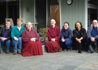 Venerable Chonyi and Venerable Jigme and lay people sitting down in front of a house.
