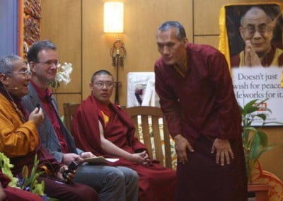 Yangsi Rinpoche, founder and president of Maitripa College bending and listening to a buddhist monk.