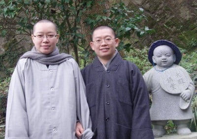Two chinese buddhist nuns pose for a photo next to a small statue