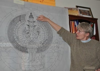 Bev Brecht explains details of the scale drawing of a Chenrezig template that she will use for her stained glass artwork for the new hall.