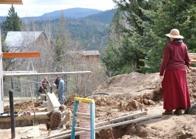 Venerable Tarpa stands on the hill overlooking the workers who are building the forms for the last of the concrete pedestals.