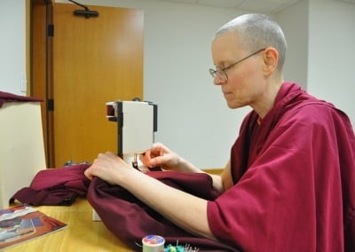 Venerable Thubten Tarpa has the auspicious task of sewing the kathina robe.
