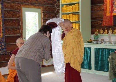 "Venerable Thubten Chodron, the virtuous nun chosen to receive the first ""robe of merit,"" touches the robe to her crown in gratitude and respect."