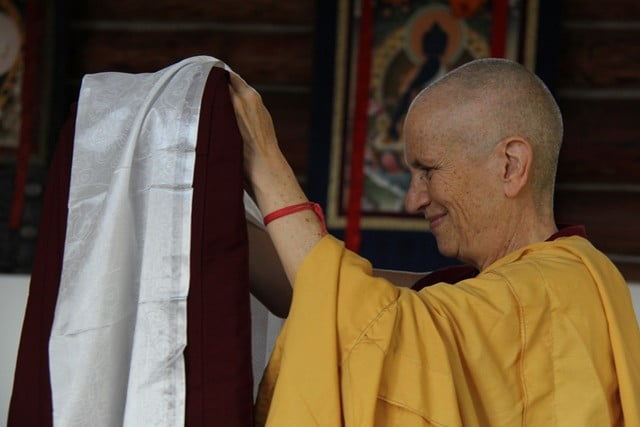Venerable Thubten Chodron covers the robe with a khata.