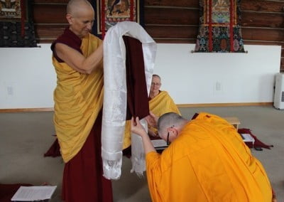 All the bhishunis (fully ordained nuns) receive the merit of the robe, and Venerable Thubten Yeshe takes her turn by touching the robe to her crown.