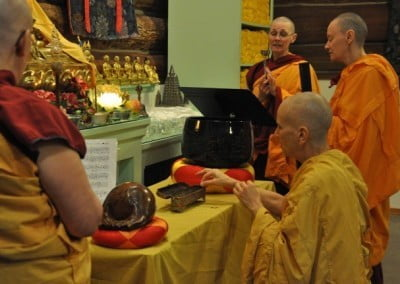 "Venerable Thubten Chodron makes the incense offering, enacting the words of the chant: ""Auspicious clouds form everywhere"" and ""the entire body of Buddhas sense it from afar."""