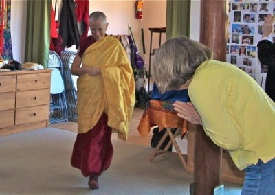 Sandy bows to welcome the Abbess into the Meditation Hall for the puja.