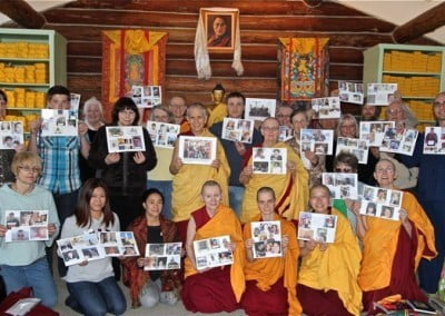 In a group photo, everyone's holding the pictures of the Retreatants from afar.