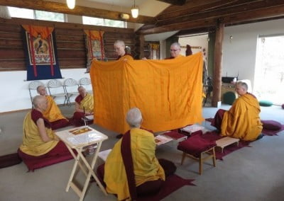 Venerables Tarpa and Yeshe display the robe of merit that Ven. Tarpa will keep on behalf of the sangha.