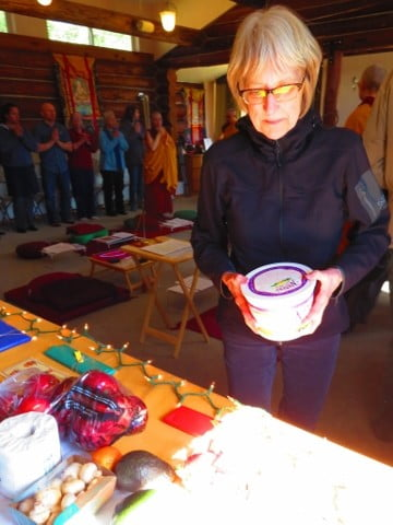 Julie places her offering to the sangha on the gift table.