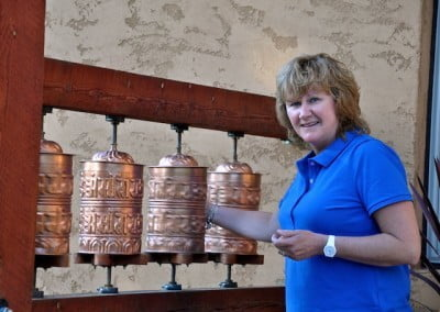 Venerable Samten's sister, Cheryl, turns the prayer wheels during her recent visit.