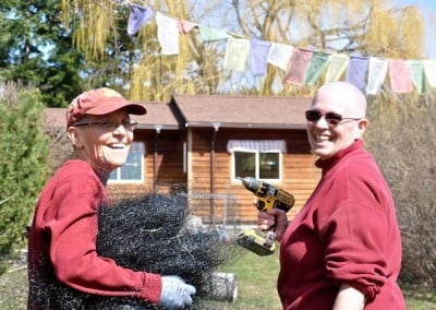 Venerables Semkye and Yeshe, armed with power tools and smile for the camera outside Venerable Chodron's cabin