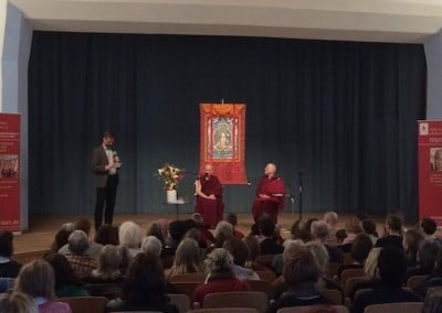 Two seated Buddhist monastics sit on stage while a man stands at a microphone.