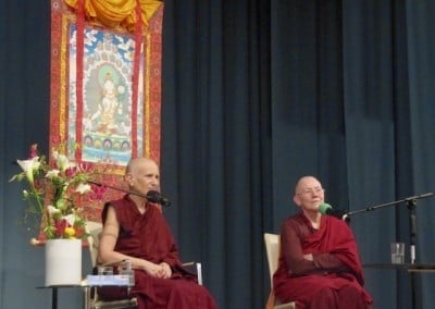Two Buddhist nuns sit on stage.