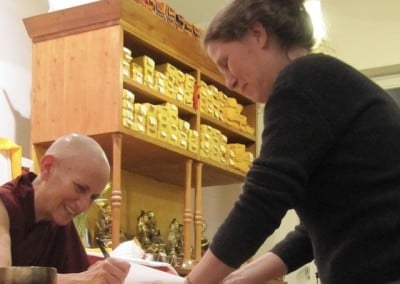 A Buddhist nun signs a book for a woman.