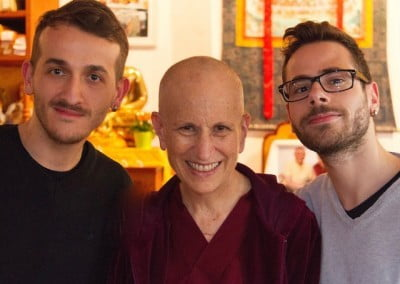 Two men and a Buddhist nun smile at the camera.