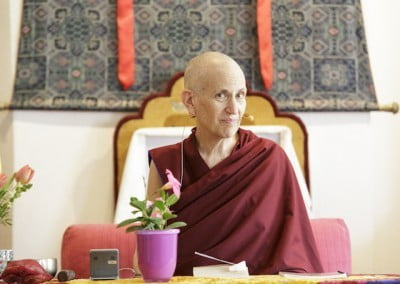 A Buddhist nun sits before a table.