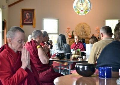 many monastics and lay people pray at tables