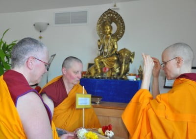 """Endowed with virtue,"" Venerable Tarpa raises the stick. One by one, each bhikshuni follows suit."