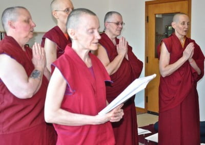 Buddhist nuns stand and chant during the ceremony