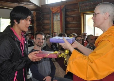 A Buddhist nun hands a gift to a lay woman