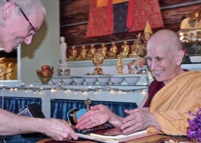 A Buddhist nun makes an offering to her teacher