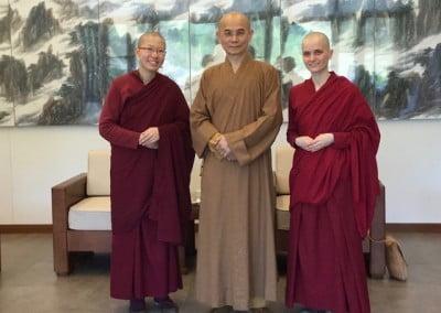 Three Buddhist monastics pose for the camera