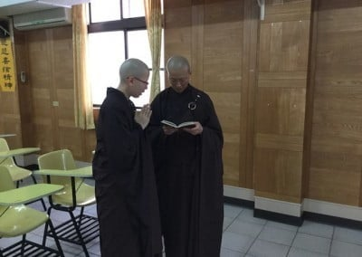 Two nuns stand together, one with hands in prayer
