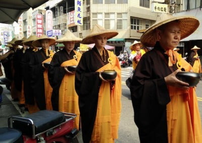 Buddhist nuns in a line holding alms bowls