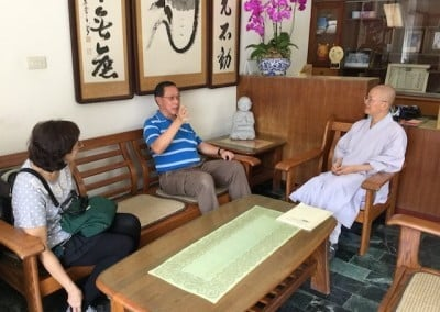 A seated woman and man speak with a seated Buddhist monastic